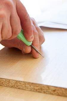 Homem faz um furo com um furador em uma folha de papelão