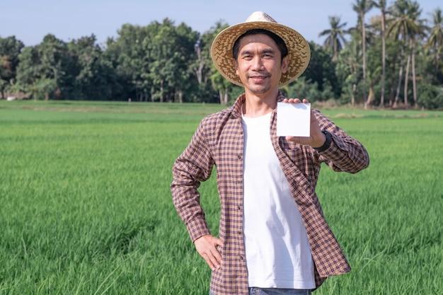 Homem fazendeiro asiático posa segurando um papel ou cartão com um rosto sorridente ao ar livre