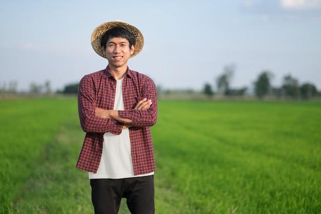 Homem fazendeiro asiático sorrindo e cruzando os braços em uma fazenda de arroz verde