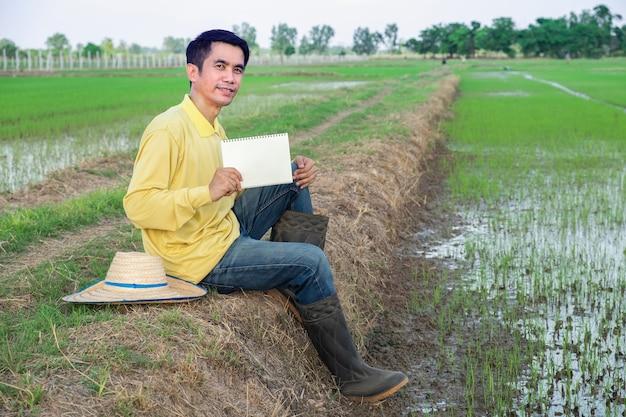 Homem fazendeiro asiático usa camisa amarela sentado e segura o caderno de papel branco na fazenda de arroz verde.