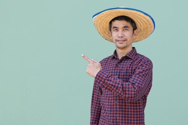 Homem fazendeiro asiático usa camisa vermelha em pé e apontando a vista lateral com fundo verde. imagem de recorte isolada.