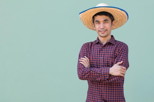 Homem fazendeiro asiático usa camisa vermelha em pé e braços cruzados com fundo verde. imagem de recorte isolada.