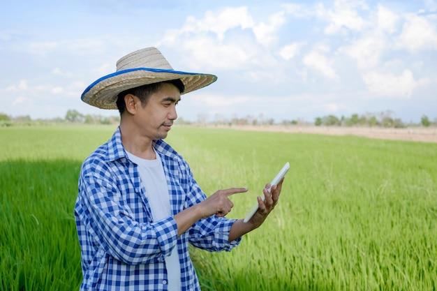 Homem fazendeiro asiático usando computador tablet smartphone na fazenda verde
