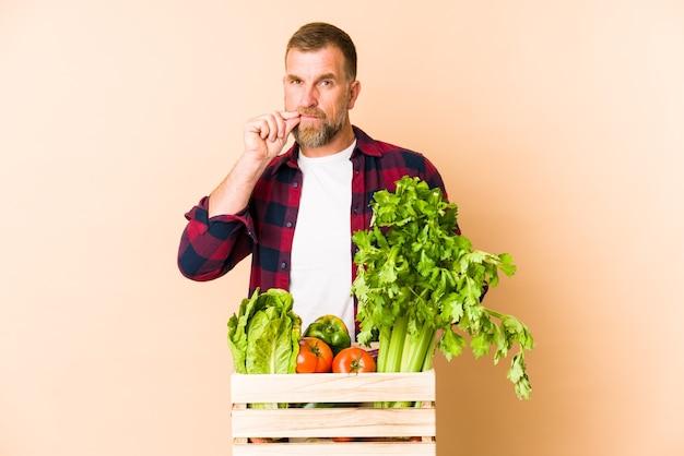 Homem fazendeiro sênior isolado em um fundo bege com os dedos nos lábios, mantendo um segredo.