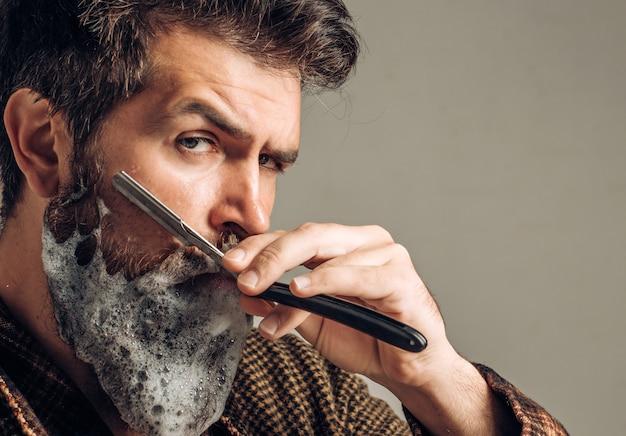 Homem fazendo a barba em casa no banheiro. conceito de barbearia.