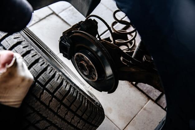 Homem fazendo a substituição do pneu ou roda com uma chave pneumática na garagem. mudando a roda do carro.