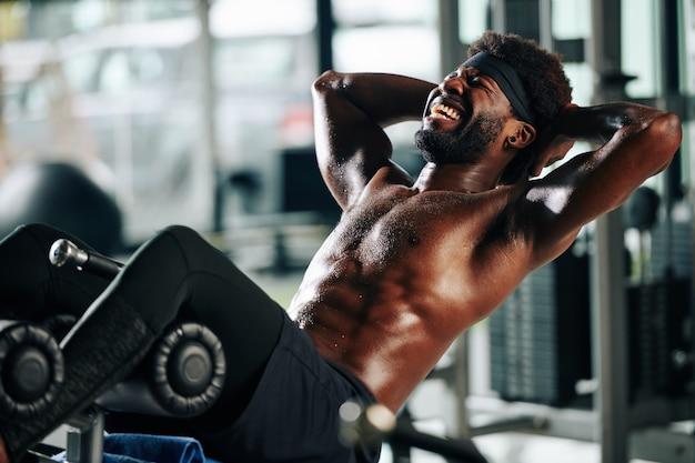 Homem fazendo abdominais do banco do ginásio