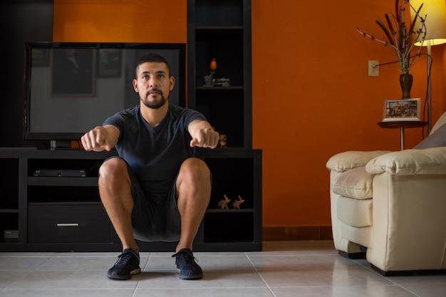 Homem fazendo agachamentos em casa na sala de estar