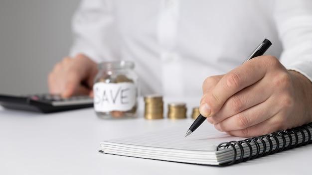 Homem fazendo anotações ao lado de um monte de moedas