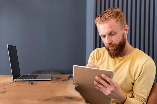 Homem fazendo anotações enquanto usa fones de ouvido