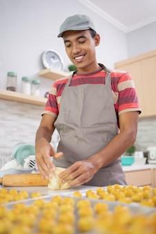 Homem fazendo bolo caseiro para vender. jovem asiático fazendo lanche de nastar em casa