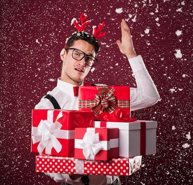 Homem fazendo caretas com uma pilha de presentes de natal