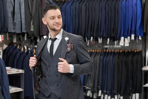 Homem fazendo compras na boutique, experimentando terno cinza elegante.