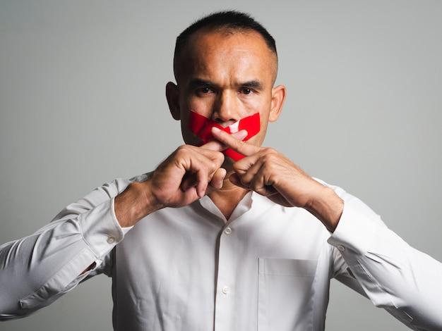 Homem fazendo dedo nos lábios silêncio gesto