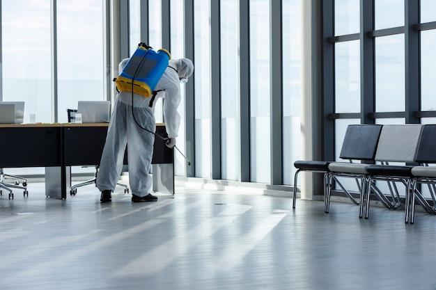 Homem fazendo desinfecção no escritório