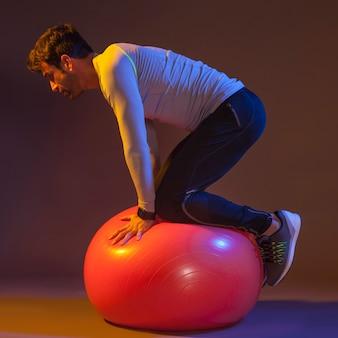 Homem fazendo exercício de equilíbrio na bola de fitness