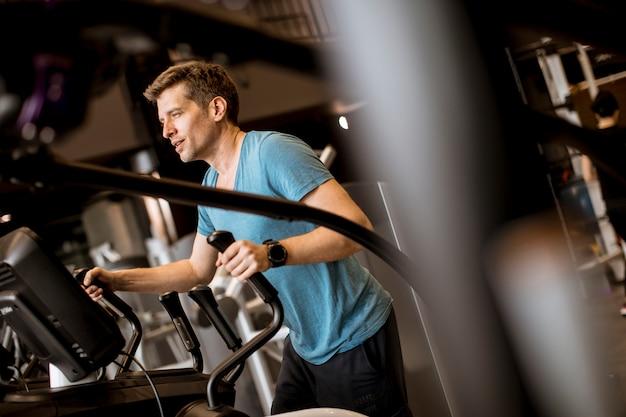 Homem, fazendo, exercício, ligado, elíptico, cruze treinador, em, desporto, condicão física, ginásio, clube
