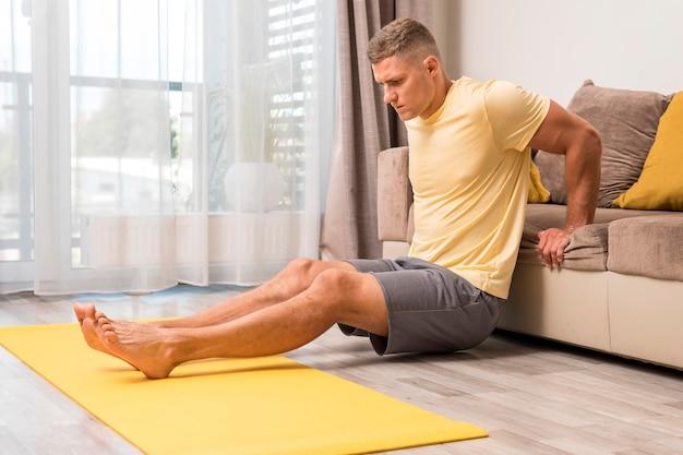 Homem fazendo exercícios em casa no sofá