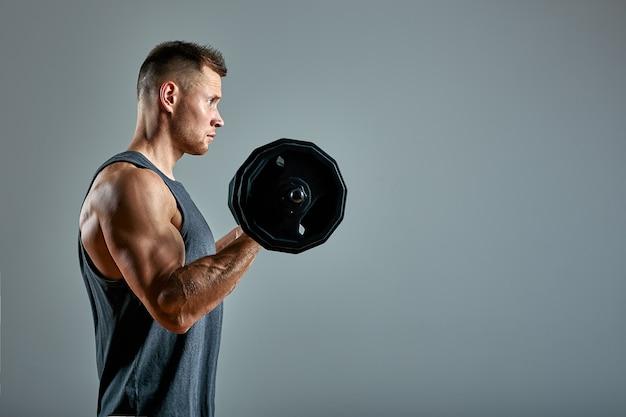 Homem fazendo exercícios nas costas, linha de barra no estúdio sobre fundo cinza. copie o espaço, banner de esporte para publicidade