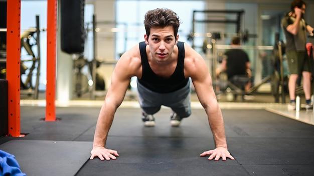 Homem fazendo flexões em uma academia