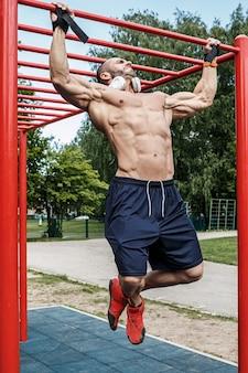 Homem fazendo flexões na barra horizontal