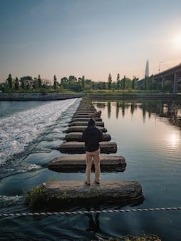 Homem fazendo fotos no rio.