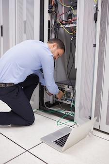 Homem fazendo manutenção e fixando fios no servidor