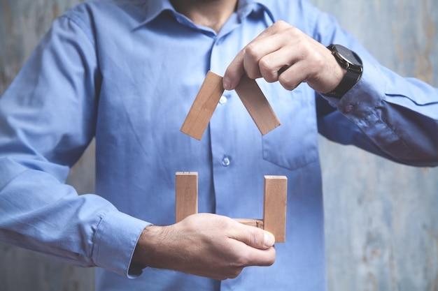 Homem fazendo modelo de casa com blocos de madeira.
