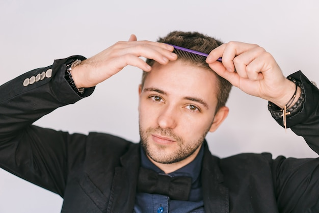 Homem fazendo penteado moderno. jovem, escovar os cabelos com pente sobre cinza