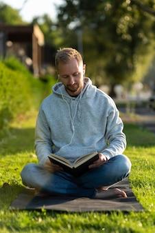 Homem fazendo posição de lótus enquanto lê um livro