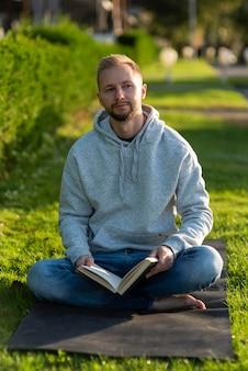 Homem fazendo posição de lótus enquanto segura um livro