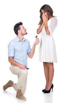 Homem fazendo propor com anel de casamento na caixa de presente.