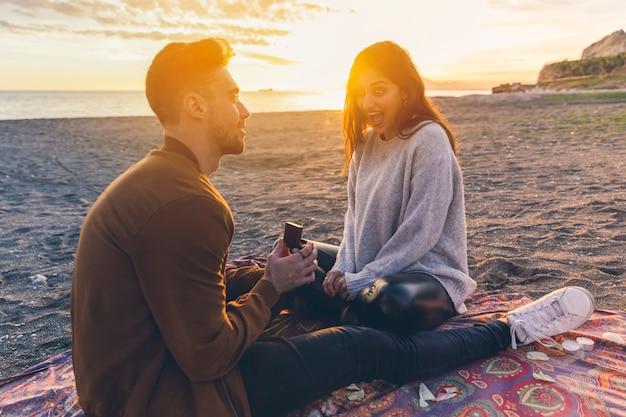 Homem fazendo proposta para mulher na beira-mar
