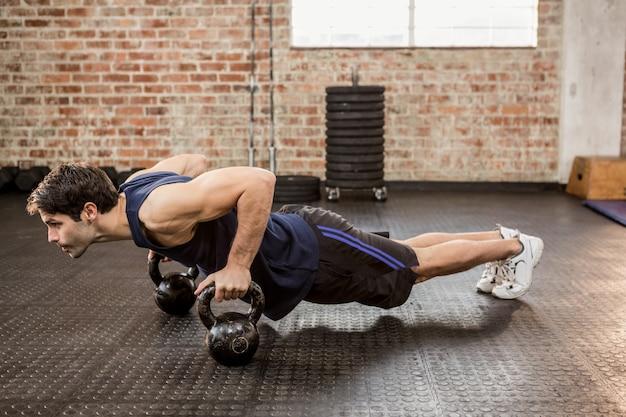 Homem fazendo push ups com kettlebell