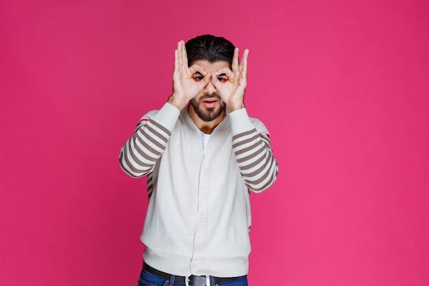 Homem fazendo rosto e olhos de coruja com os dedos.