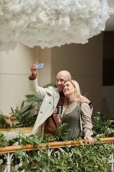 Homem fazendo selfie retrato no celular com uma jovem durante o encontro na varanda