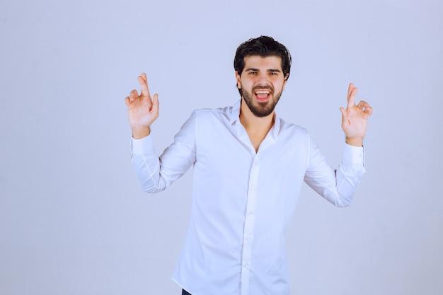 Homem fazendo sinal com a mão cruzada.