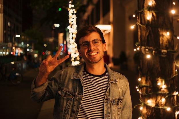 Homem fazendo sinal de paz e sorriso