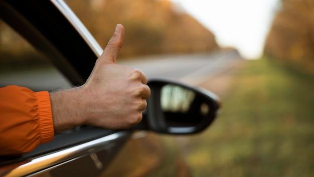Homem fazendo sinal de positivo para fora do carro durante uma viagem