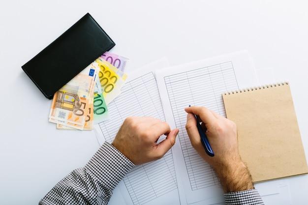 Homem fazendo sua contabilidade. empréstimo de depósito de poupança e taxa de juros. as notas de euro estão empilhadas.