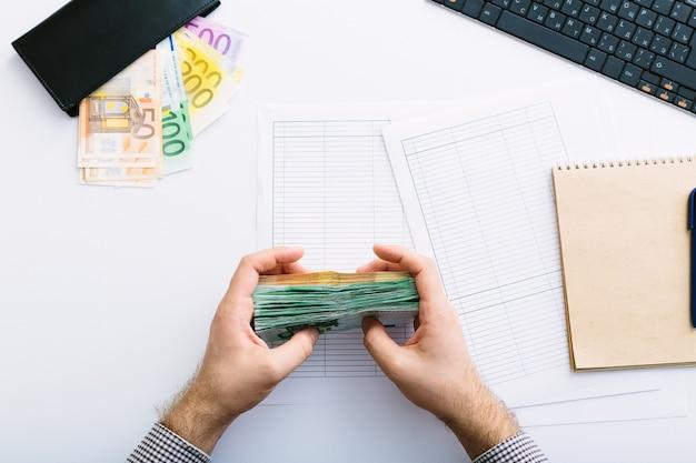 Homem fazendo sua contabilidade. fechar as mãos do homem com o dinheiro do euro, formulário de relatório fiscal, finanças, conceito bancário de economia