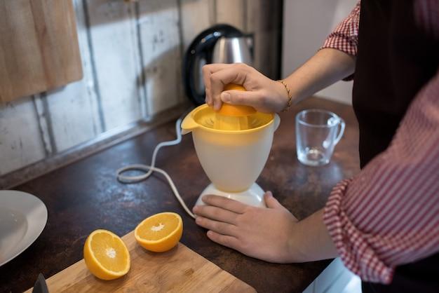 Homem fazendo suco de laranja