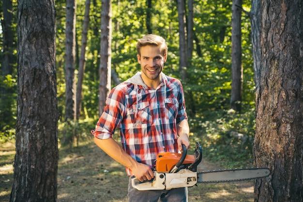 Homem fazendo trabalho de homem feliz marceneiros lenhador lenhador com motosserra no fundo da floresta agricu ...