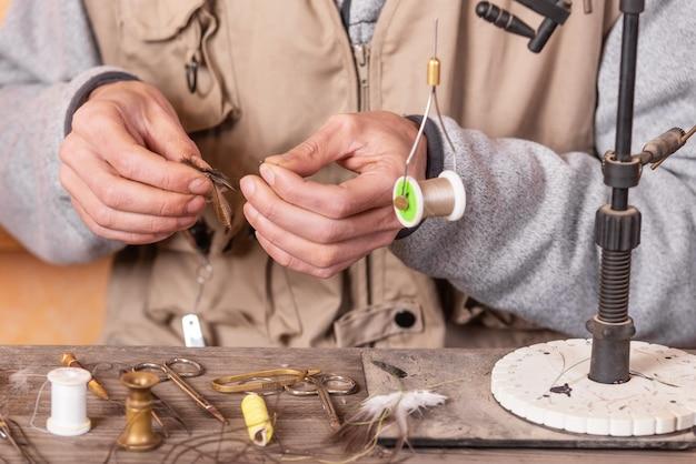 Homem fazendo truta voa. voar amarrando equipamentos e materiais para a preparação da pesca com mosca.