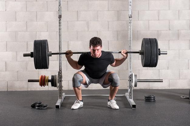 Homem fazendo um exercício de agachamento nas costas crossfit