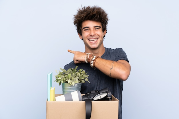 Homem fazendo um movimento ao pegar uma caixa cheia de coisas apontando o dedo para o lado