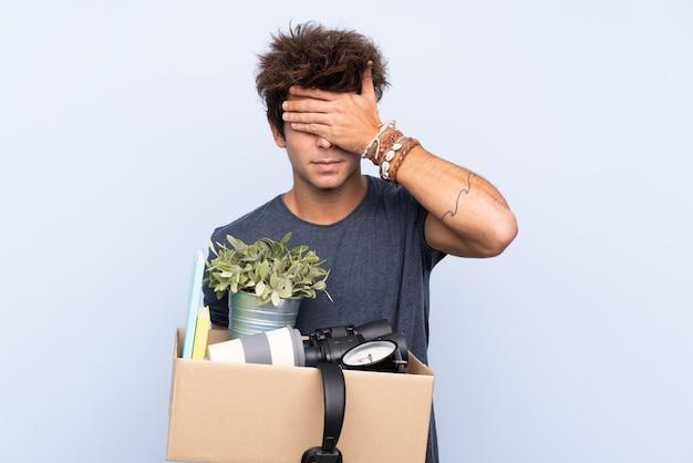 Homem fazendo um movimento ao pegar uma caixa cheia de coisas cobrindo os olhos pelas mãos