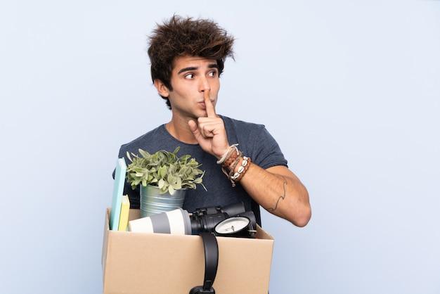 Homem fazendo um movimento ao pegar uma caixa cheia de coisas fazendo o gesto de silêncio