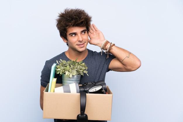 Homem fazendo um movimento ao pegar uma caixa cheia de coisas ouvindo algo