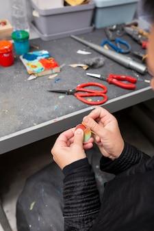 Homem fazendo um pedaço de madeira colorida à mão